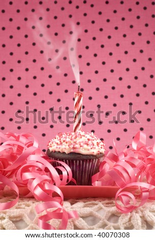 birthday cupcake with one smoking candle, pink ribbons and background ...
