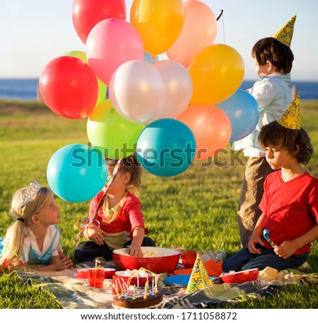 A birthday picnic with kids and balloons