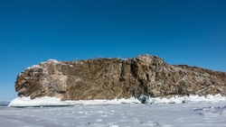 A bizarre rocky granite island devoid of vegetation rises above a frozen lake. The base is covered with icicles. Snow on ice. Clear blue sky. Baikal