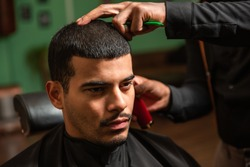 A black African-American barber cuts and shaves the hair of a Hispanic Latino man with a goatee and mustache with an electric razor in a barber shop.