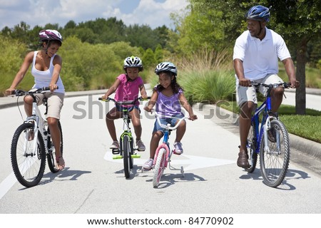 A Black African American family of two parents and two children, two girls, cycling together.