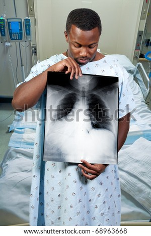 A black African American man patient holding an x-ray