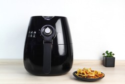 a black air fryer or oil free fryer appliance is on the wooden table in the kitchen with deep fried banana chips and small plant in the pot ( air fryer ) during dinner with happy family member in home