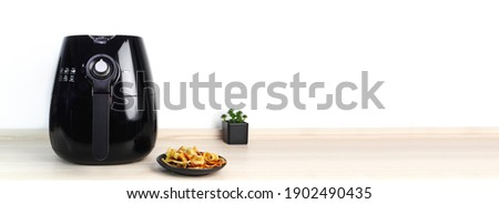 a black air fryer or oil free fryer appliance is on the wooden table in the kitchen with deep fried banan chips and small plant in the pot on white cement wall background during dinner in the party