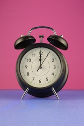 A black alarm clock over a colorful background.
