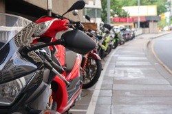 A black and red motrorbike lined in a row parking on the side of a street. Photographed with a shallow depth of field in the daytime
