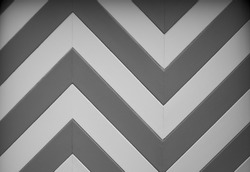 a black and white chevron or zig zag wood design of a garage door on an older home