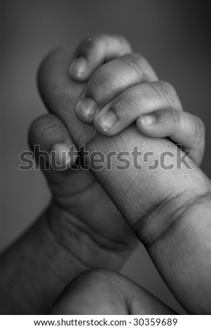 A black and white close-up of a preemie's hand holding his dad's finger