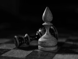 A black and white close-up of two old chess pieces on the board: queen is lying and bishop is standing near it
