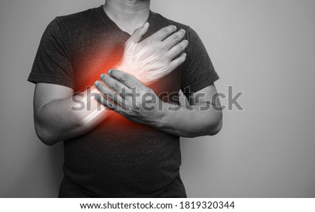 A black and white image Closeup of male arms holding his painful wrist  From arthritis symptoms or Carpal Tunnel Syndrome (CST) Medical healthcare concept. Сток-фото ©