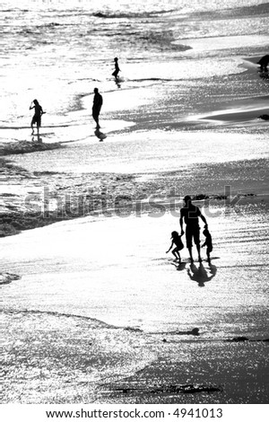 A black and white image of a father and his children playing in the surf at sunset