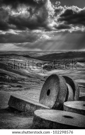 A black and white image of a group of millstones lie abandoned at the site where they were carved by hand from the hard Millstone Grit of the Peak District.