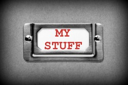 A black and white image of a metal drawer label holder with a white index card and the title My Stuff added in red text