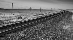 A black and white image of a railroad in the desert with a telegraph line and mountains in the backgroud.