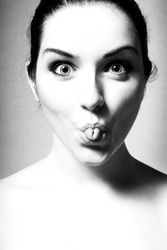 A black and white image of a young woman pulling a funny face by rolling her tongue.