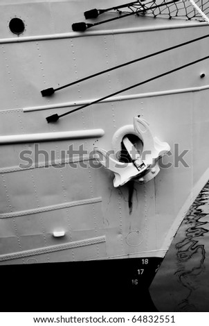 a black and white image of and anchor on a ship tied up in a harbor.