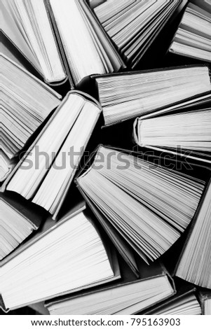 A black and white image of hardback books or text books from above. Books and reading are essential for self improvement, gaining knowledge and success in our careers, business and personal lives #795163903