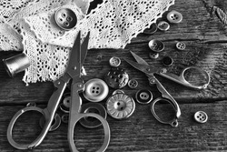 A black and white image of vintage buttons with scissors and old delicate lace.