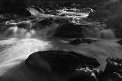 A black and white long exposure image of a waterfall on Ey Burn in the Scottish Highlands.  The smoothed out water flows between and around the dark rocks in the river bed.