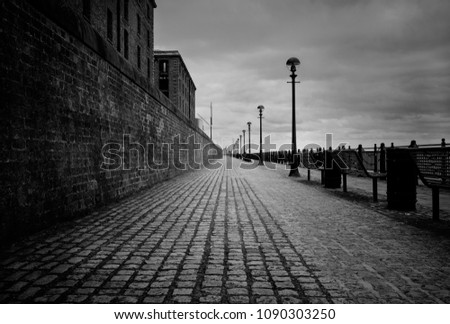 A black and white photo in the center of a cobblestone path on the Liverpool waterfront. The eerie sky fills the sky and a red brick wall aligns the left side of the photo.