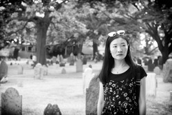 A black and white photo of a chinese woman looking somber in the burying point cemetery in Salem Massachusetts.