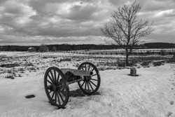 A black and white photo of a Civil War cannon in the snow at the Gettysburg National Military Park battlefield in Pennsylvania where union and confederate soldiers battled in July of 1863.