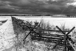 A black and white photo of a Civil War era fence in the snow at the Gettysburg National Military Park on the field of Pickett's Charge in Pennsylvania.