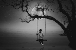 A black and white photo of a woman sitting on a swing and watching the full moon by the sea alone.
