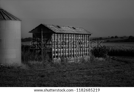 A black and white photo of an abandoned barn. A silo sits next to the barn in this Midwest landscape.