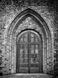 A black and white photo of an arched doorway to a gothic style church.