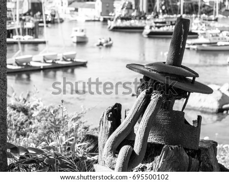 A black and white photo of an old rusty boat anchor on a hill overlooking a harbor  #695500102