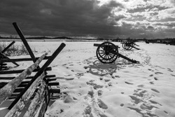 A black and white photo of Civil War cannons in the snow at the Gettysburg National Military Park on the field of Pickett's Charge.