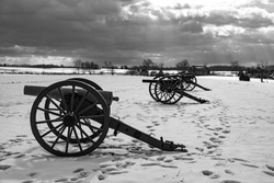 A black and white photo of Civil War cannons in the snow at the Gettysburg National Military Park on the field of Pickett's Charge in Pennsylvania.
