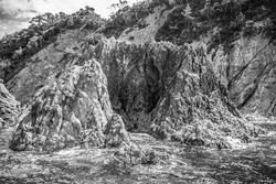 A black and white photo of unique, steep, jagged rocky islands rising out of the Japan Sea near a scenic, rugged mountain coastline.