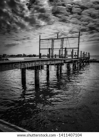 A black-and-white photograph of a dock in Margate, New Jersey with a dark twist. Stormy clouds above give it a moody feel. #1411407104