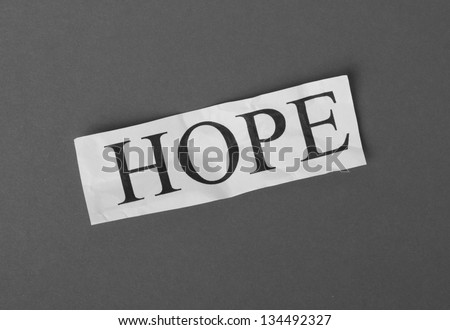 A black and white photograph of the word Hope typed on a scrap of crumpled white paper resting on a dark, textured paper background