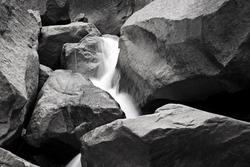 A black and white photograph of water streaming down rocks at Yosemite Falls in Yosemite National Park.
