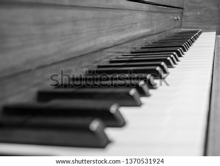 A black and white pic of a an piano keyboard waiting for someone to play.