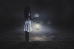 A black and white picture, a little girl holding a lantern in the street alone