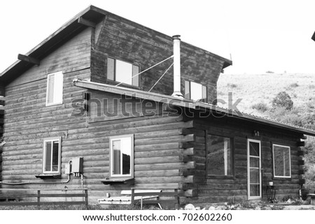 A black and white picture of a log cabin.