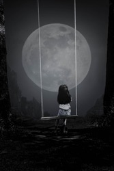 A black and white picture of a young woman riding a swing looking at the full moon in the lonely night