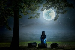A black and white picture. The little girl sat and looked at the moon on a log by the sea on a full moon night beautifully.