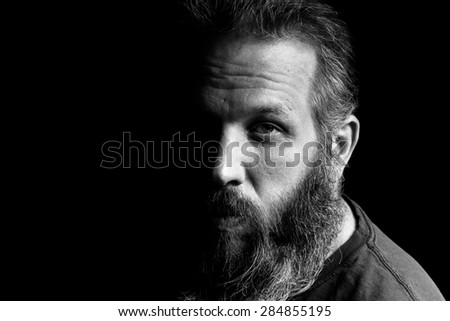 A Black and white portrait of a bearded man in front of a black background. High Contrast.