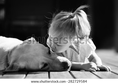 A black and white portrait of a little cute toddler girl kissing her dog, a yellow labrador relaxing on the wooden deck in the sun