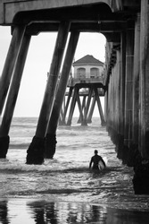 A black and white shot looking out from under the Huntington Beach Pier at a surfer walking into the surf on a cold winter day.