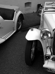 A black and white shot of old retro roadster cars parked on the street