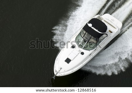 A black and white speedboat shot from above while travelling fast.