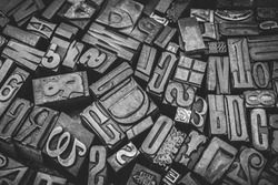 A black and white textured background of a heap of antique wooden type-setting letter blocks with various fonts, upper- and lowercase, antique letters used for printing books and newspapers.