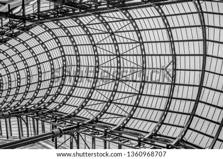 A black and white view of the metal framework and glass covered roof over the Galleria, Southwark,London