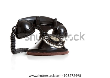 A black antique telephone on a white background with copy space